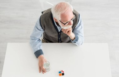 Overhead view of pensive man looking away, sitting behind table with pills and water in glass stock vector