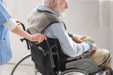 Cropped view of nurse standing behind disabled senior man in wheelchair