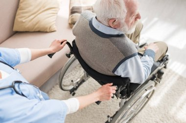High angle view of nurse standing behind disabled gray haired man in wheelchair