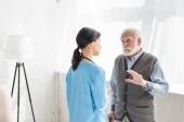 Uomo anziano in piedi dentro casa con spazio copia, e parlando con linfermiera
