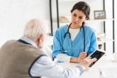Muž v důchodu používající digitální tablet, který sedí s vážným lékařem v místnosti