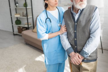 Cropped view of grey haired man standing with nurse in bright room