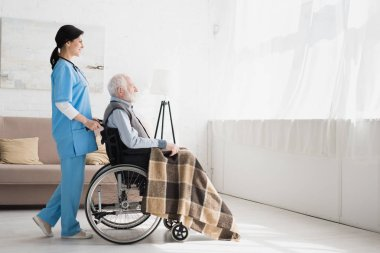 Side view of happy nurse standing in room with copy space, and carrying about disabled grey haired man in wheelchair