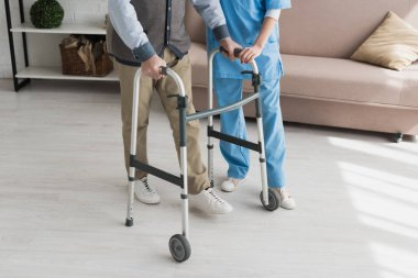 Senior man walking with nurse, and recovering from injury