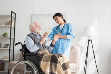 Nurse talking to disabled and happy grey haired man in wheelchair