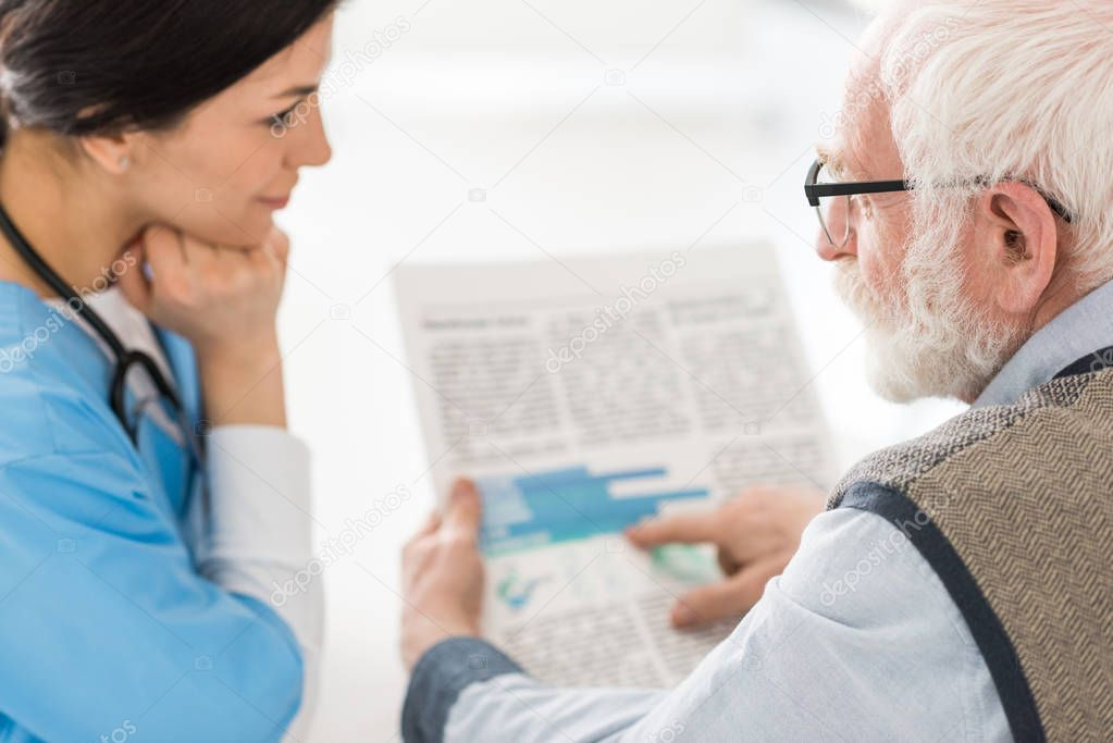 Selective focus of grey haired man talking with nurse, holding newspaper in hands stock vector