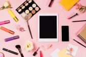 Photo top view of digital tablet and smartphone with blank screen, notebooks, flowers and decorative cosmetics on pink