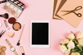 pohled na digitální tablet s prázdnou obrazovkou, květiny a dekorativní kosmetické prostředky na růžovém
