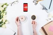 Kyiv, Ukrajna-május 11, 2019: vágott kilátás nő csésze kávé, fánk és okostelefon YouTube app képernyőn a munkahelyen
