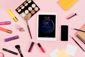 KYIV, UKRAINE - MAY 11, 2019: top view of digital tablet with lock screen, smartphone with blank screen, highlighters and decorative cosmetics on pink