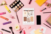 KYIV, UKRAINE - MAY 11, 2019: top view of digital tablet with pinterest app on screen, smartphone with blank screen, flowers, highlighters and decorative cosmetics on pink