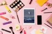 Kyiv, Ukrajna-május 11, 2019: felülnézet digitális tabletta Tumblr app a képernyőn, okostelefon, üres képernyő, virágok, highöngyújtók és dekoratív kozmetikumok rózsaszín