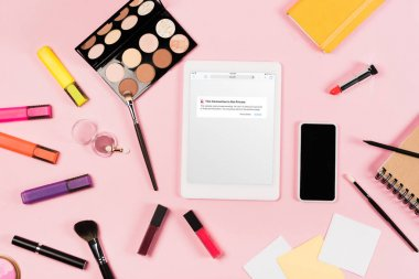 KYIV, UKRAINE - MAY 11, 2019: top view of digital tablet with vk app on screen, smartphone with blank screen, highlighters and decorative cosmetics on pink stock vector