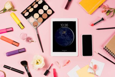 KYIV, UKRAINE - MAY 11, 2019: top view of digital tablet with lock screen, smartphone with blank screen, flowers, highlighters and decorative cosmetics on pink