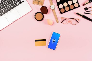 KYIV, UKRAINE - MAY 11, 2019: top view of laptop, decorative cosmetics, glasses, wristwatch, credit card and smartphone with shazam app on screen on pink stock vector