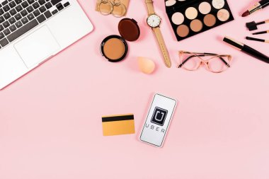 KYIV, UKRAINE - MAY 11, 2019: top view of laptop, decorative cosmetics, glasses, wristwatch, credit card and smartphone with uber app on screen on pink stock vector