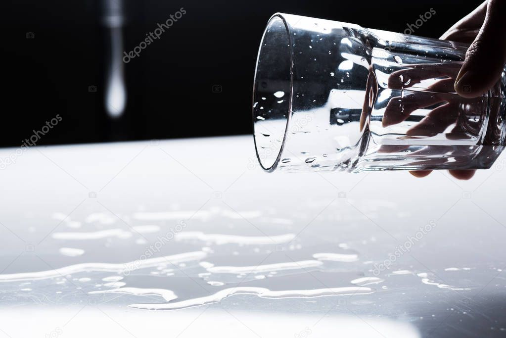 cropped view of woman holding glass and water spots on light surface