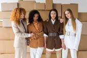 beautiful multicultural women posing near boxes on white