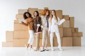 pretty young multicultural women posing near boxes on white