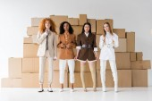 attractive multicultural girls posing near boxes on white