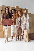 beautiful multicultural girls standing with suitcases near boxes on white