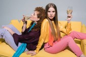 attractive redhead girl drinking champagne near blonde young woman on white