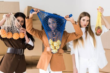 african american women covering faces while holding string bags with fruits near blonde girl on white