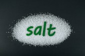 a zöld papírra vágott só a sókristályon, fekete alapon