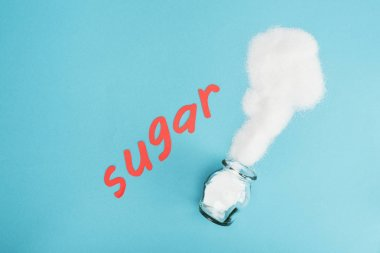 top view of red paper cut word sugar near sugar crystals and glass jar on blue background