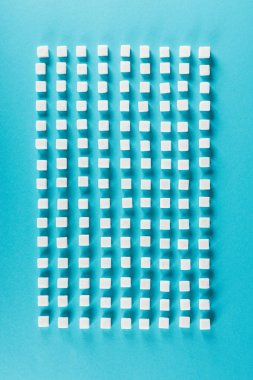Top view of white sugar cubes arranged in rows on blue surface stock vector