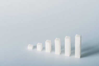 Stacks of white sugar cubes on grey background with copy space stock vector