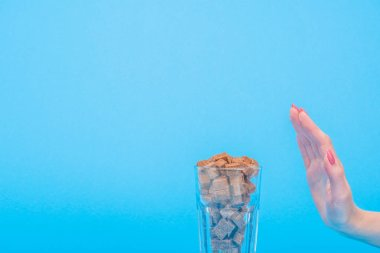 cropped view of woman showing refuse gesture near glass with brown sugar cubes isolated on blue