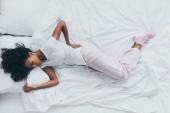 pohled na Africkou ženu, která trpí bolestí zad a leží na bílých lůžkovcích