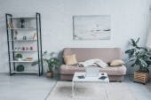 geräumiges Wohnzimmer mit Sofa, Regal, Pflanzen und Tisch mit digitalen Geräten