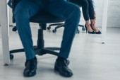 Photo cropped view of african american businessman sitting in office near colleague suffering from pain in leg