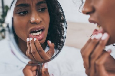 young african american woman looking at mirror while suffering from tooth pain