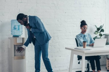 thirsty african american manager standing near water cooler near colleague sitting at workplace