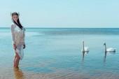 Erwachsene Frau im weißen Schwanenkostüm steht in Fluss in der Nähe von Vögeln