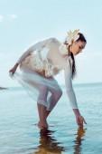Elegante Frau im weißen Schwanenkostüm, die Fluss berührt und Wasser betrachtet