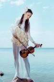 gyengéd nő fehér hattyú jelmez hegedű állva kék folyó és az ég háttérben