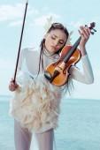 gyengéd nő fehér hattyú jelmez állt a kék ég háttér hegedűre