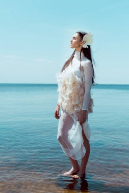 young woman in white swan costume standing on river and sky background, closing eyes