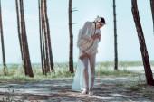 schöne Frau im weißen Schwanenkostüm steht am Sandstrand in der Nähe von Bäumen