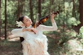 Fotografie brunette woman in white swan costume standing on forest background, playing on violin, looking away