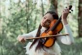 felnőtt nő fehér hattyú jelmez állva az erdő háttérben, hegedűre játszik