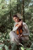 fiatal nő fehér hattyú jelmez áll a földön hegedűvel, nézi kamera