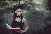 pohled na krásnou ženu v čarodějnické maškarě stojící na pozadí lesa, s červenou knihou, s pohledem stranou