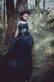 elegantní žena v čarodějnické maškarní s korunou na hlavě