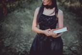 oříznutý pohled ženy na čarodějnické kostýmy stojící na pozadí lesa s červenou knihou