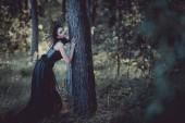 elegantní žena v čarodějové kroji stojící poblíž kmene stromů a dívala se na kameru